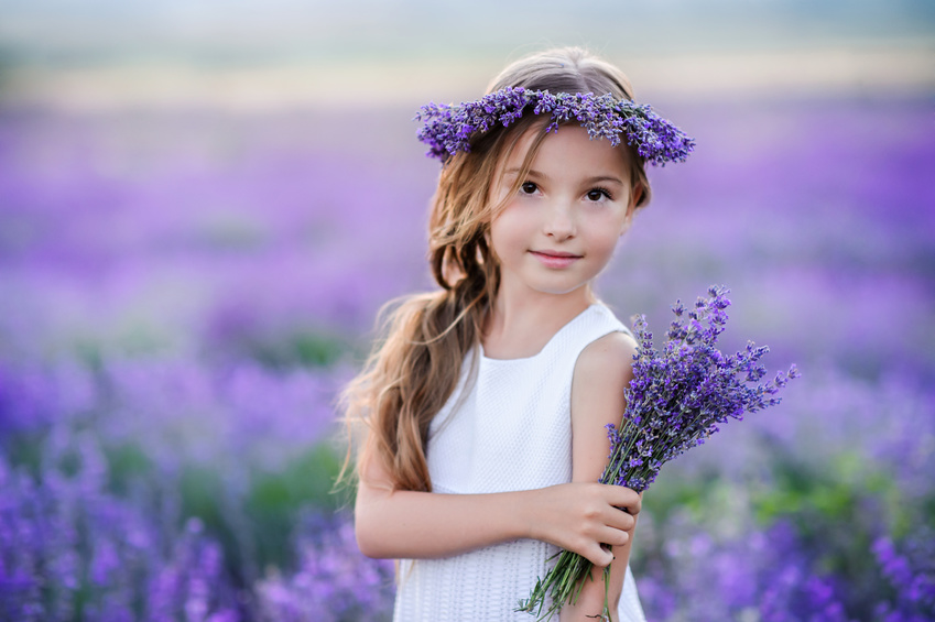 Beautiful girl in a field of lavender on sunset. Girl in amazing dress walk on the lavender field.